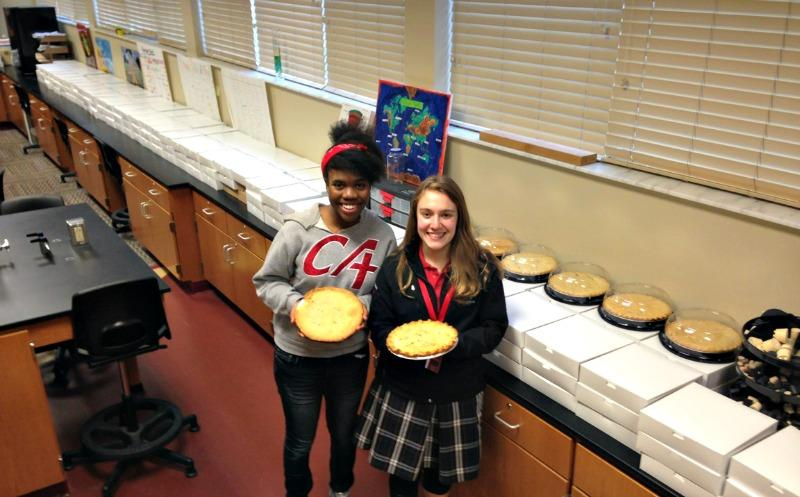 Sophomore Danielle Azard and junior Rebekah Kuhlman stand in front of the many boxes of pies prepared by chemistry students
