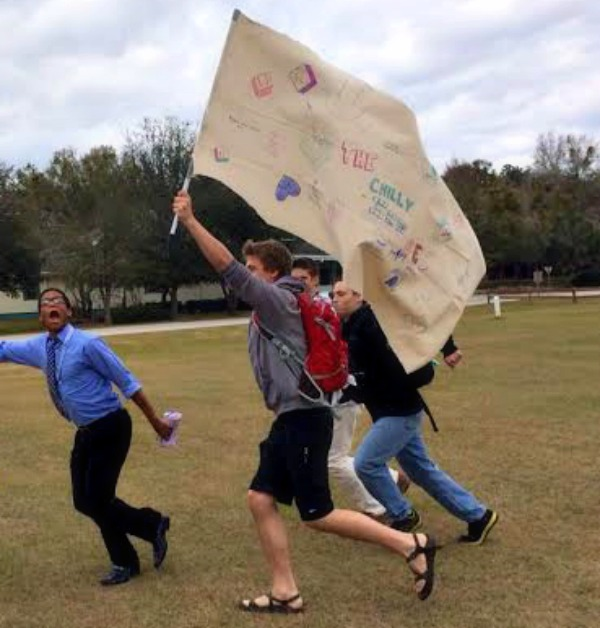 Senior Andrew Suekert (with flag) runs with his Prayer Conference group