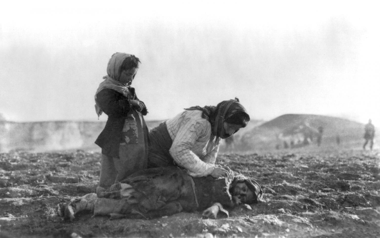 An Armenian woman kneels beside her dead child. Photo via Wikimedia Commons